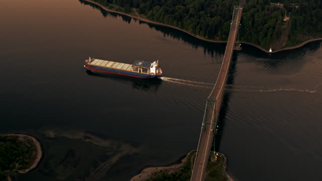 AERIAL Cargo ship entering the Vancouver Harbour at the Lions Gate Bridge at sunset