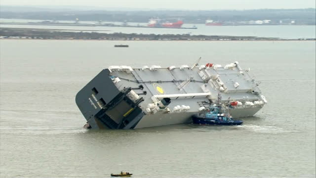 salvage teams assess damage air view of car transporter ship hoegh osaka listing badly to one side after being run aground to prevent it capsizing... - capsizing stock videos and b-roll footage