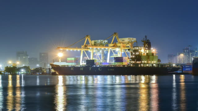 Cargo ship in the harbor at full moon