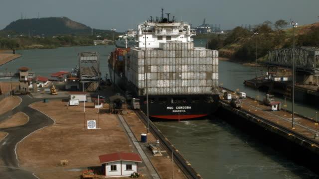 cargo ship makes its way through the miraflores locks as it crosses the panama canal on april 7, 2016 in panama city, panama. a $5.3 billion panama... - パナマ運河点の映像素材/bロール