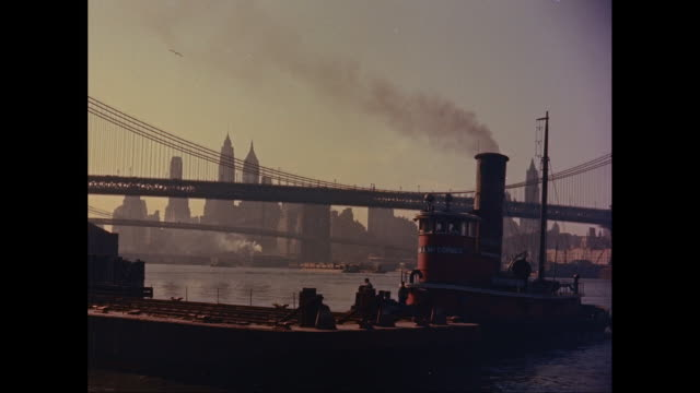 ws cargo ship moving on east river, skyline with manhattan bridge and brooklyn bridge in background / new york city, new york state, united states - 1960 stock videos & royalty-free footage