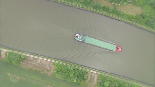aerial ws ds cargo ship moving on river / kiel canal, schleswig-holstein, germany - schleswig holstein stock-videos und b-roll-filmmaterial