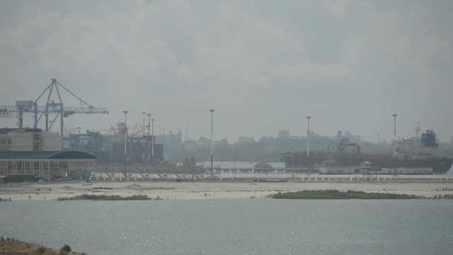 a cargo ship navigates a river inlet as a worker lays a brick path at the mombasa standard gauge railway terminal at km 0 where goods coming from... - inlet stock videos & royalty-free footage