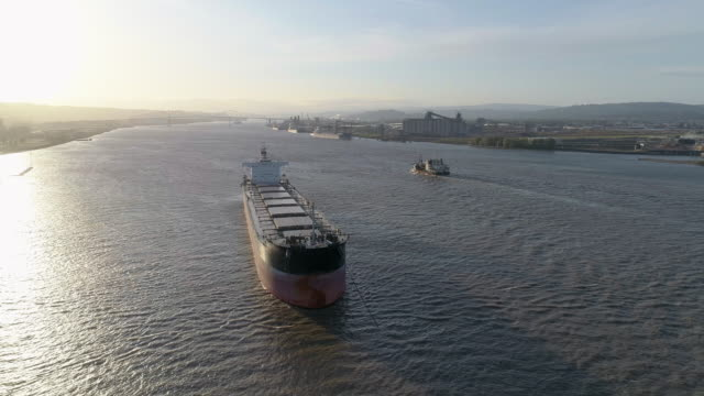 cargo ship on anchorage at columbia river, on the border between states oregon and washington, usa. a small boat passing in the backdrop. drone aerial low altitude video with the panning camera motion. - cascade range stock videos & royalty-free footage