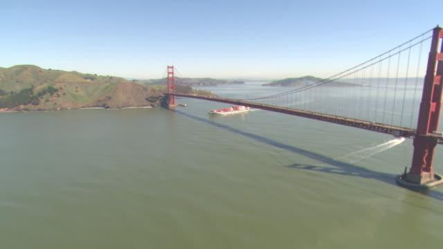 A cargo ship on San Francisco Bay passes under Golden Gate Bridge.