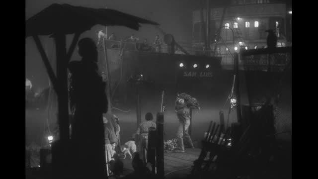 vidéos et rushes de cargo ship pulls into harbor at night, crew and longshoremen working, dock filled with bananas. cargo ship pulls into foggy harbor at night on... - docker