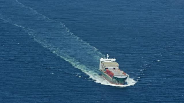 aerial cargo ship sailing across the sea in sunshine - cargo ship stock videos & royalty-free footage