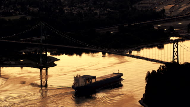 AERIAL Cargo ship sailing below the Lions Gate Bridge in the light of the setting sun