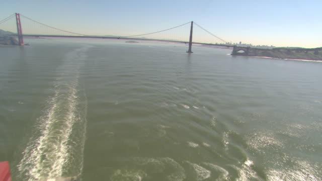 A cargo ship sails away from Golden Gate Bridge in San Francisco Bay.