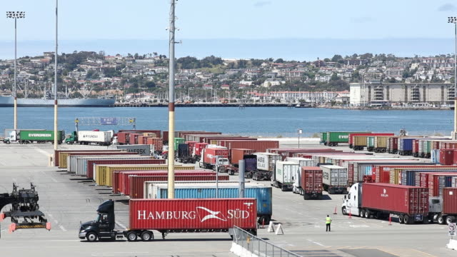 cargo shipping containers are unloaded at the a.p. moeller-maersk a/s apm terminals shipping terminal at the port of los angeles in los angeles,... - 大型トレーラー点の映像素材/bロール