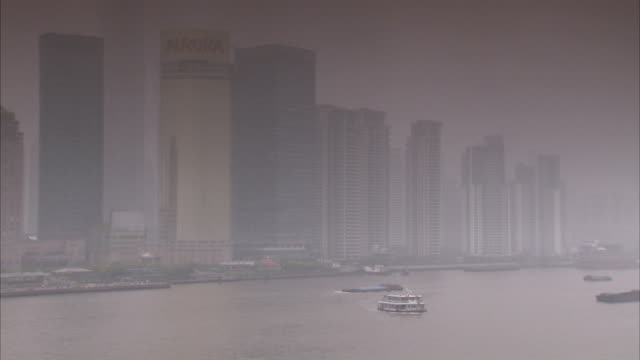 Cargo ships float along the Huangpu River in Shanghai, China. Available in HD.