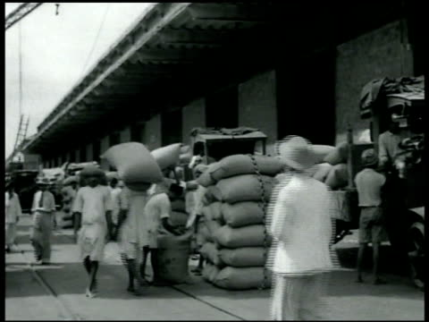 Cargo ships in harbor Stacks of sacks at docks ready for export ship being loaded by men carrying sacks LS Docks w/ people stacks of sacks