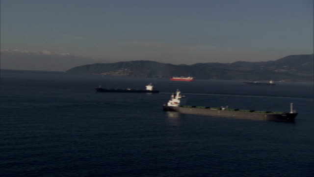 cargo ships sail past the andalusian coast into the mediterranean sea. available in hd. - andalusien stock-videos und b-roll-filmmaterial