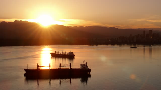 aerial cargo ships sailing in burrard inlet in vancouver at sunset - distant stock videos & royalty-free footage