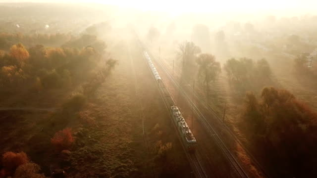cargo train at sunrise in the fog. view from the drone - schienenverkehr stock-videos und b-roll-filmmaterial