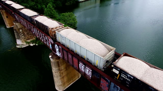 Cargo train bringing minerals and supplies across the colorado river on a bridge to Austin , Texas