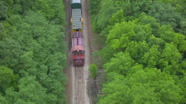 WS TS AERIAL POV Cargo train moving along tracks and passes by trees Bass point creek / Iowa, United States