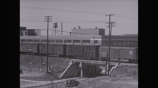 ws cargo train moving near automobile industry / united states - telegraph pole stock videos and b-roll footage