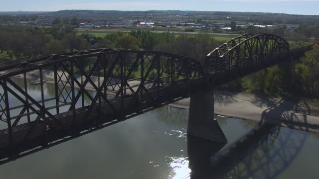 WS AERIAL POV Cargo train moving over Northern Pacific Railroad Bridge / Bismarck, North Dakota, United States