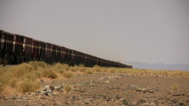 ws slo mo cargo train moving through sahara desert /  zouerat, tiris zemmour, mauritania - モーリタニア点の映像素材/bロール