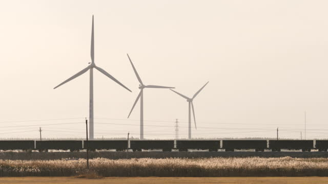 cargo train passes wind power plant - schienenverkehr stock-videos und b-roll-filmmaterial