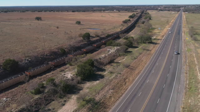 cargo train passing on a railroad along a highway in savanna grassland on edwards plateau, the arid highland in texas, usa. aerial drone video with the forward camera motion, following the train. - rural scene stock videos & royalty-free footage