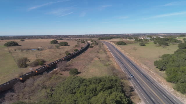 vídeos de stock e filmes b-roll de cargo train passing on a railroad along a highway in savanna grassland on edwards plateau, the arid highland in texas, usa. aerial drone video with the forward camera motion, following the train. - texas