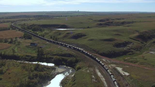 ws aerial pov cargo train passing through farmlands / north dakota, united states - güterzug stock-videos und b-roll-filmmaterial