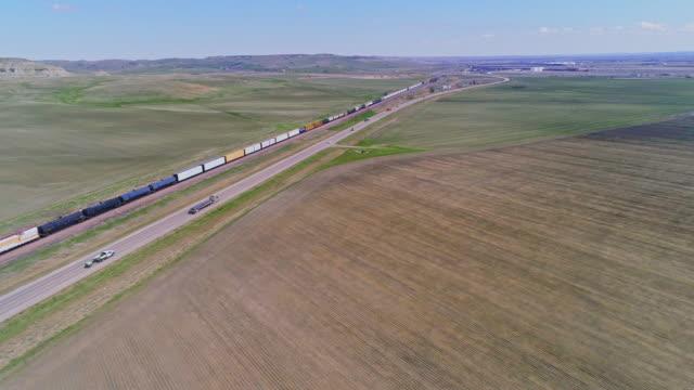 vidéos et rushes de train de fret passant par des champs près de williston, dakota du nord, au début du printemps. des voitures et des camions circulent sur une autoroute le long du chemin de fer. vidéo de drone aérien avec le mouvement avant de caméra suivant le train. - dakota du nord