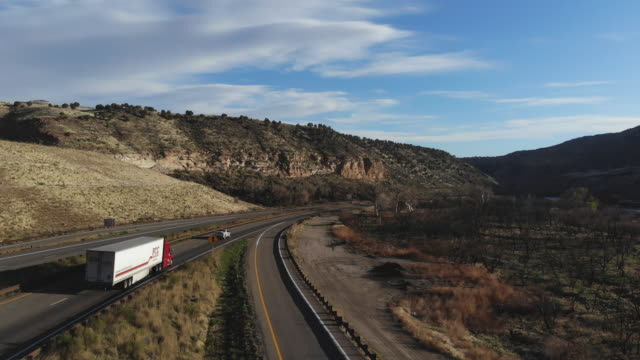 cargo transport long haul semi truck on a rural western usa interstate highway 4k video - main road stock videos & royalty-free footage