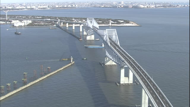 a cargo vessel sails beneath the tokyo gate bridge. - ariake sea stock videos and b-roll footage