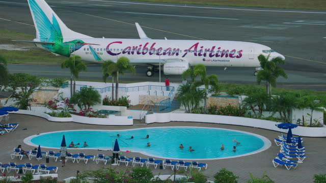 ws caribbean airlines plane taxiing on taxiway, people enjoying in swimming pool in foreground / st. maarten - taxiway stock-videos und b-roll-filmmaterial