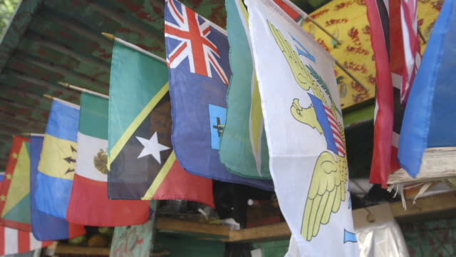 vídeos de stock e filmes b-roll de caribbean flags hanging from storefront in brooklyn, medium shot - dia do trabalhador