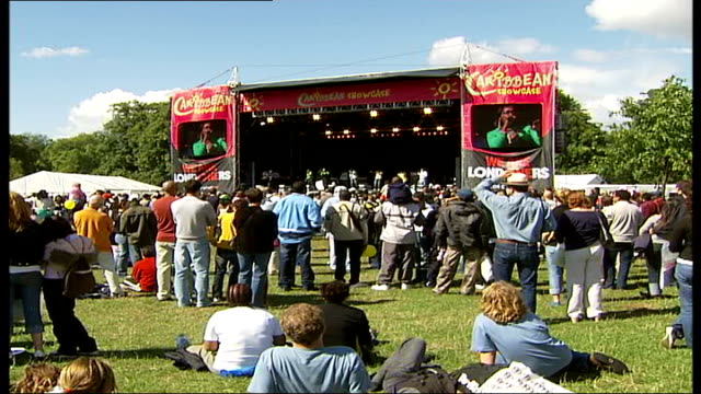 vidéos et rushes de caribbean showcase festival held in hyde park; england: london: hyde park: ext general view of festivalgoers including children, audience watching... - audience de festival