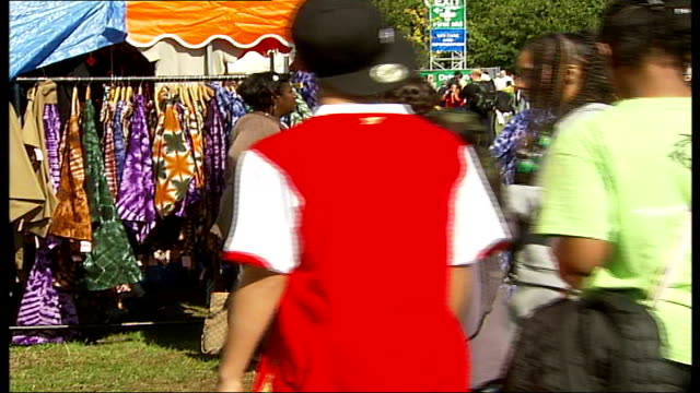 vidéos et rushes de caribbean showcase festival held in hyde park; police officers chatting with crowd, shoppers at craft stalls, browsing through racks of clothing,... - audience de festival