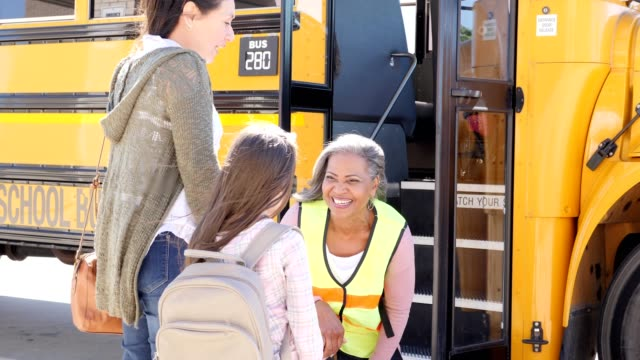 Caring bus driver talks to young girl on her first day of school
