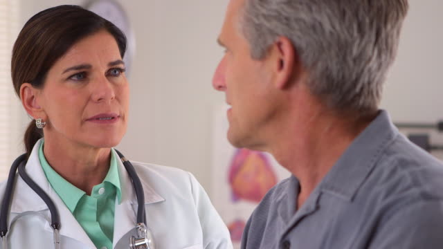 Caring doctor talking with elderly patient
