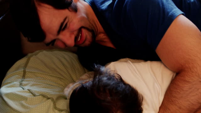 Caring Father Playing Peekaboo Game with Baby Daughter