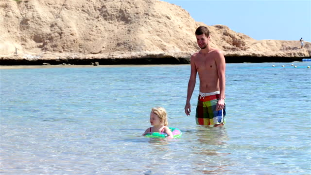 caring father watching his daughter as she swims in the sea. - sinai egitto video stock e b–roll