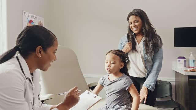 vídeos de stock, filmes e b-roll de pediatra do sexo feminino carinhoso conversa com paciente em idade pré-escolar - clínica médica