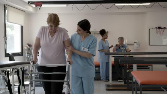 vídeos y material grabado en eventos de stock de terapeuta femenina cariñosa ayudando a una mujer mayor a caminar con un caminante de movilidad durante la rehabilitación física - edificio médico