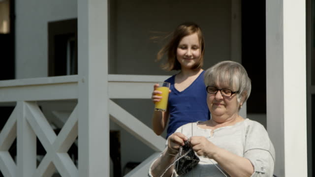 caring for elderly grandchild is bringing orange juice to old grandmother who is knitting and smiling together outdoors on sunny day at the house porch of terrasse shot on red camera - porch stock videos and b-roll footage