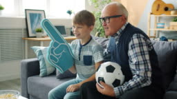 Caring grandad and happy boy watching football on TV holding foam hand and ball