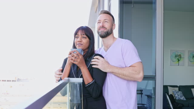 caring husband brings a cup of coffee for wife at the balcony - life during covid-19 lockdown - flat stock videos & royalty-free footage