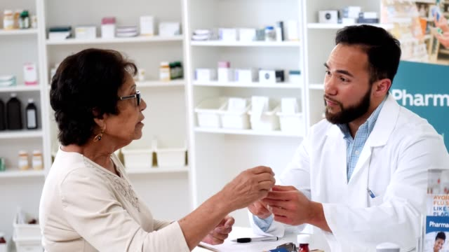 caring male pharmacist reviews senior customer's prescription - pharmacy stock videos & royalty-free footage