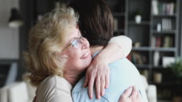 Caring mature old mum hugging adult son expressing mothers love