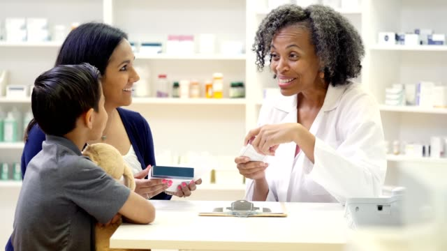 caring mature pharmacist explains drug side effects to mid adult mom - asking stock videos & royalty-free footage
