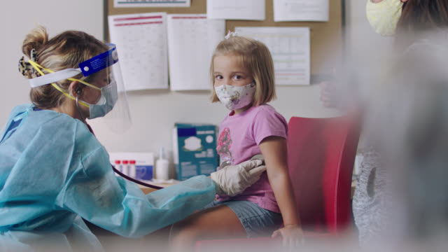 caring medical professional in medical clinic uses stethoscope to listen to young girl's heart and lungs - guanto indumento protettivo video stock e b–roll