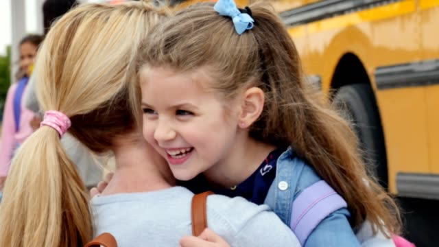 Caring mom hugs daughter before the girl boards school bus for her first day of kindergarten