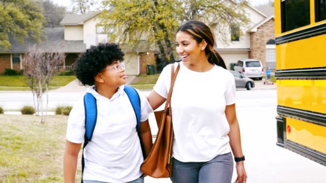 caring mom walks son to school bus stop - first day of school stock videos & royalty-free footage